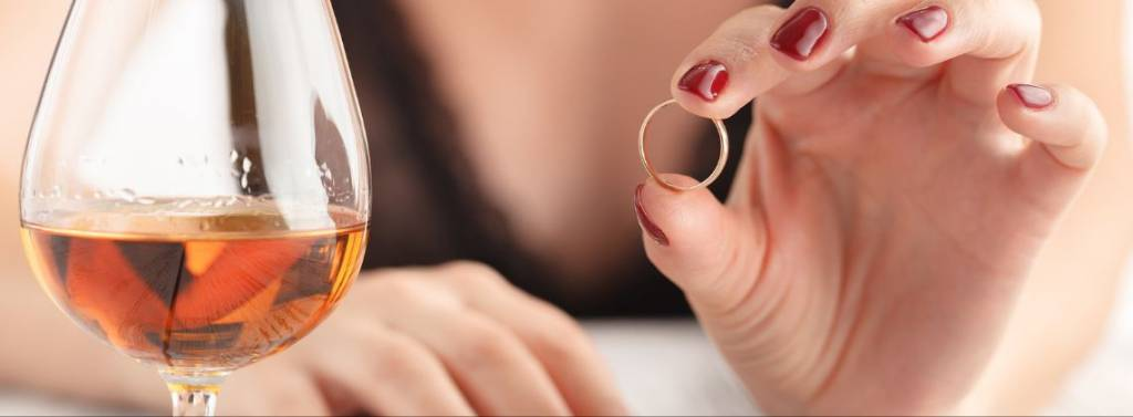 woman taking her ring off and looking at it to signify a divorce
